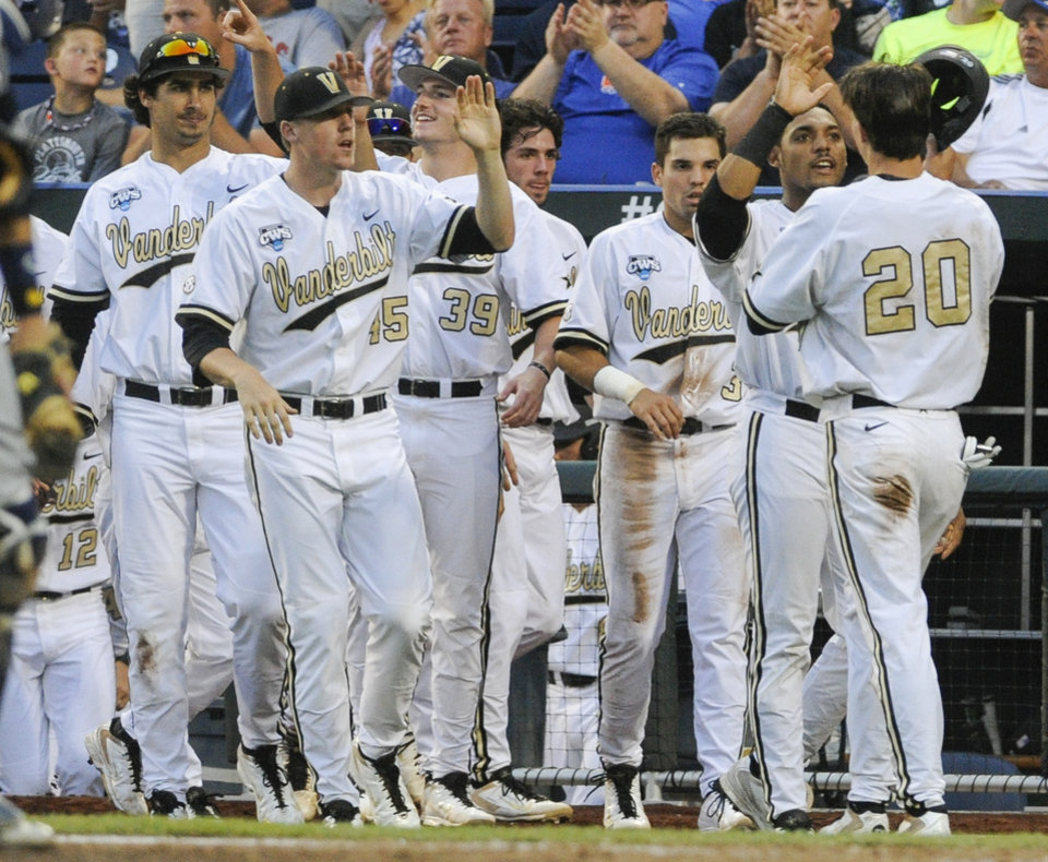 Photo - Vanderbilt's Bryan Reynolds (20) is greeted at the dugout after he scored against UC Irvine on a double by Zander Wiel in the fifth inning of an NCAA baseball College World Series game in Omaha, Neb., Monday, June 16, 2014. (AP Photo/Eric Francis)