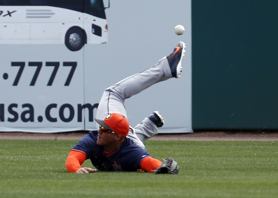 Photo - Houston Astros right fielder George Springer can't catch a hit by Washington Nationals' Ian Desmond in the first inning of a spring exhibition baseball game, Friday, March 7, 2014, in Viera, Fla. (AP Photo/Alex Brandon)