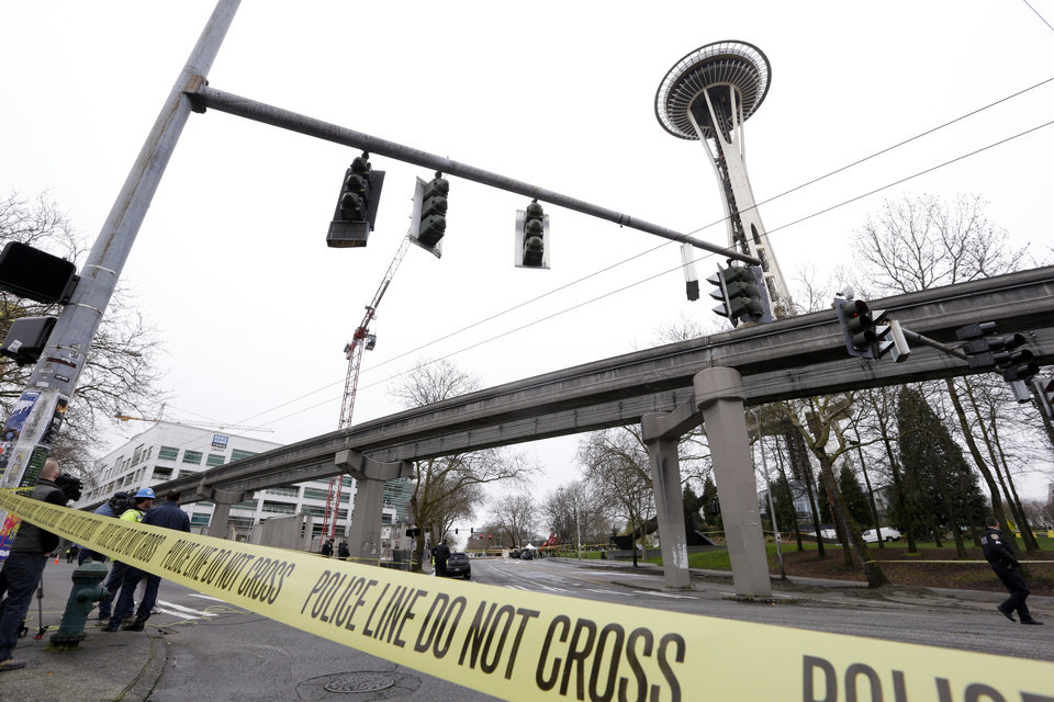 Photo - With the KOMO-TV broadcast building at left, authorities attend to the scene of a news helicopter crash near the Space Needle, Tuesday, March 18, 2014, in Seattle. Two people were killed and another critically injured. (AP Photo/Elaine Thompson)
