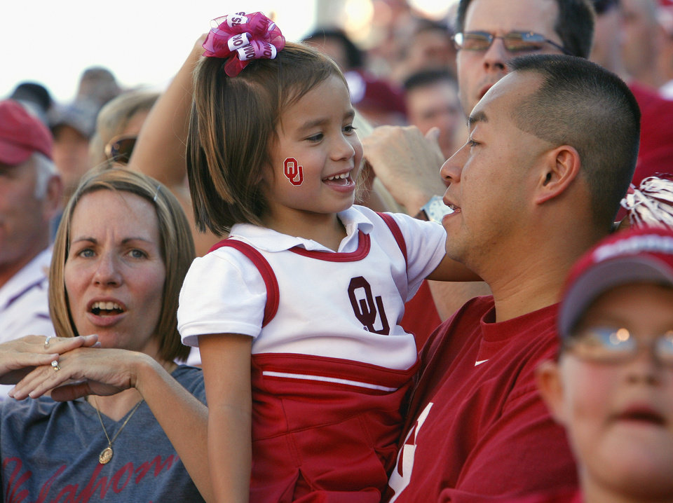 Photo - Stephanie and Hai Bui and daughter Amy (4) watch the college football game between the University of Oklahoma Sooners (OU) and Utah State University Aggies (USU) at the Gaylord Family-Oklahoma Memorial Stadium on Saturday, Sept. 4, 2010, in Norman, Okla.   Photo by Steve Sisney, The Oklahoman
