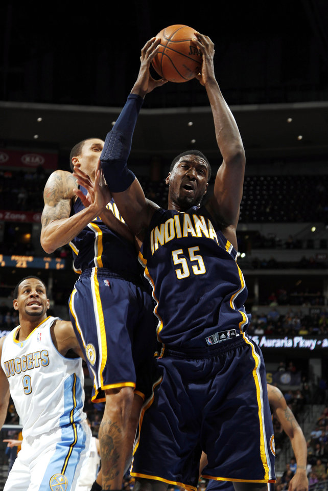 Photo - Indiana Pacers center Roy Hibbert, front right, pulls in a rebound in front of Pacers guard George Hill, front left, and Denver Nuggets guard Andre Iguodala, back, in the first quarter of an NBA basketball game in Denver on Monday, Jan. 28, 2013. (AP Photo/David Zalubowski)