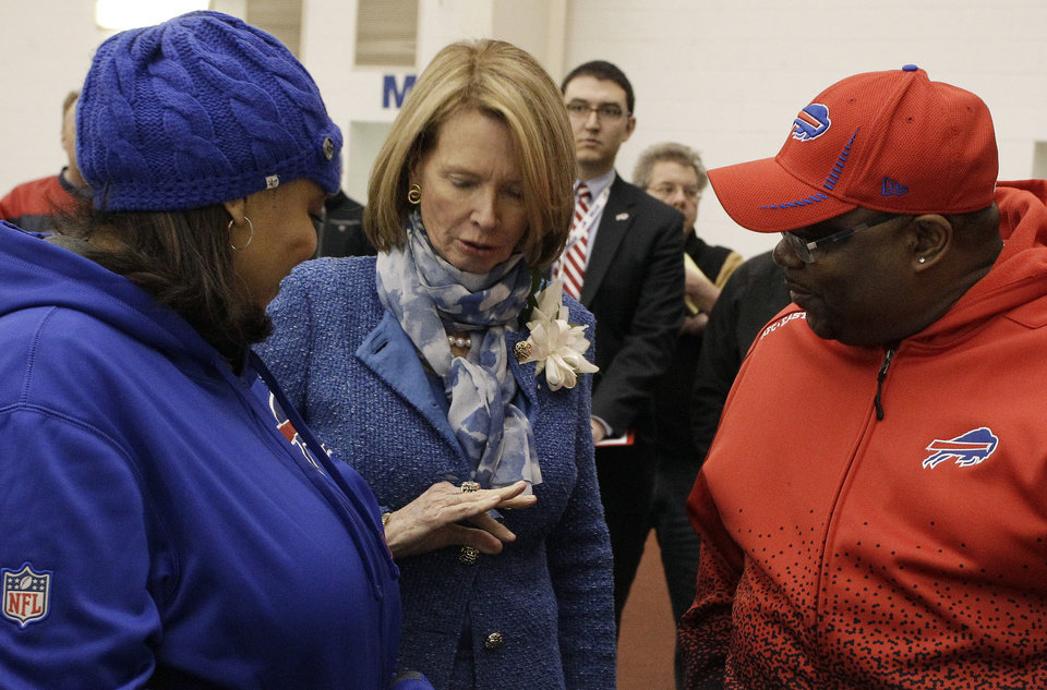 Photo - Mary Wilson, center, shows her late husband's Hall of fame ring to Buffalo Bills fans Regina Moultrie, left, and Dennis Brown, of Buffalo, during a public memorial and remembrance being held inside the NFL football team's fieldhouse for Buffalo Bills owner Ralph C. Wilson in Orchard Park, N.Y., Saturday, April 5, 2014. Wilson, the team's founder and sole owner, died March 25. (AP Photo/Nick LoVerde)