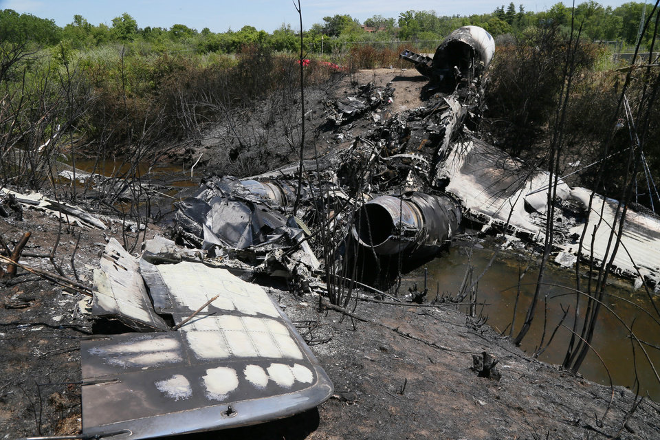 Photo - Wreckage lies at the scene Monday, June 2, 2014, in Bedford, Mass., where a plane plunged down an embankment and erupted in flames during a takeoff attempt at Hanscom Field Saturday night. Lewis Katz, co-owner of the Philadelphia Inquirer, and six other people died in the crash. (AP Photo/Boston Herald, Mark Garfinkel, Pool)