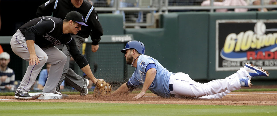 Photo - Kansas City Royals' Mike Moustakas is out at third by Colorado Rockies third baseman Nolan Arenado as he tried to steal during the second inning of a baseball game Wednesday, May 14, 2014 in Kansas City, Mo. (AP Photo/Charlie Riedel)
