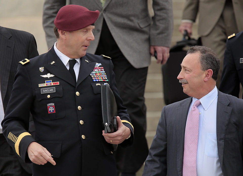 Photo - Brig. Gen. Jeffrey Sinclair, left, who admitted to inappropriate relationships with three subordinates, leaves court while talking with his defense attorney Richard Scheff, right, at Fort Bragg, N.C., Wednesday, March 19, 2014.  Closing arguments were presented Wednesday, but no sentence was reached.  (AP Photo/Ted Richardson)