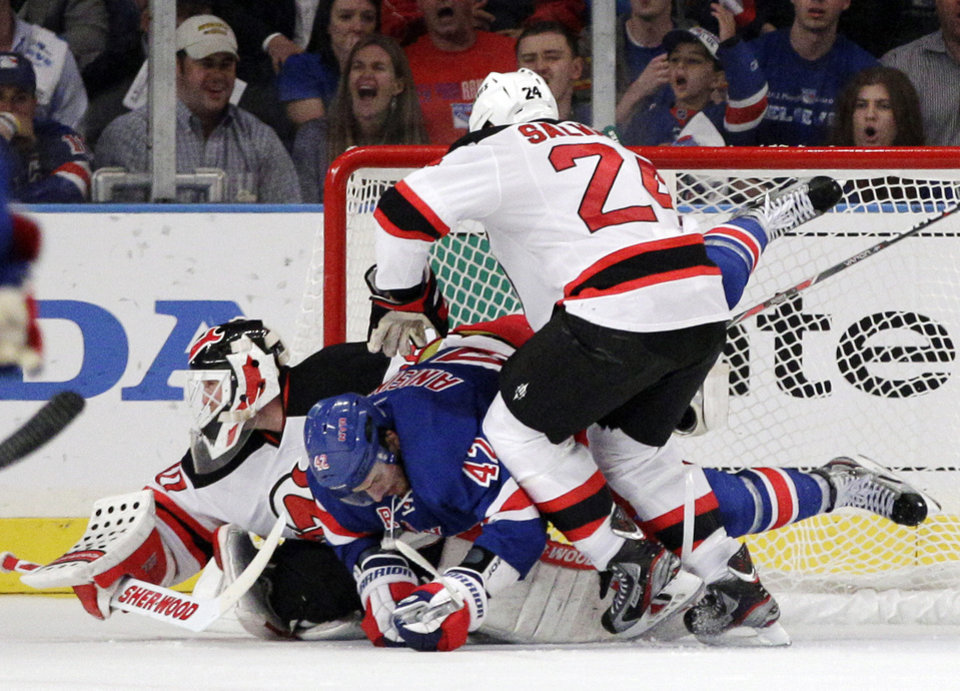 Photo -   New York Rangers' Artem Anisimov, center, of Russia, falls on New Jersey Devils goalie Martin Brodeur as Bryce Salvador approaches during the third period of Game 5 of an NHL hockey Stanley Cup Eastern Conference final playoff series, Wednesday, May 23, 2012, in New York. The Devils won 5-3. (AP Photo/Frank Franklin II)