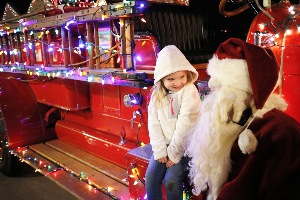 Photo -  Madison Porter, 5, talks with Santa while sitting on a 1929 firetruck during during Winter Night at the Children's Safety Village in Edmond. PHOTO BY DOUG HOKE, THE OKLAHOMAN   DOUG HOKE -