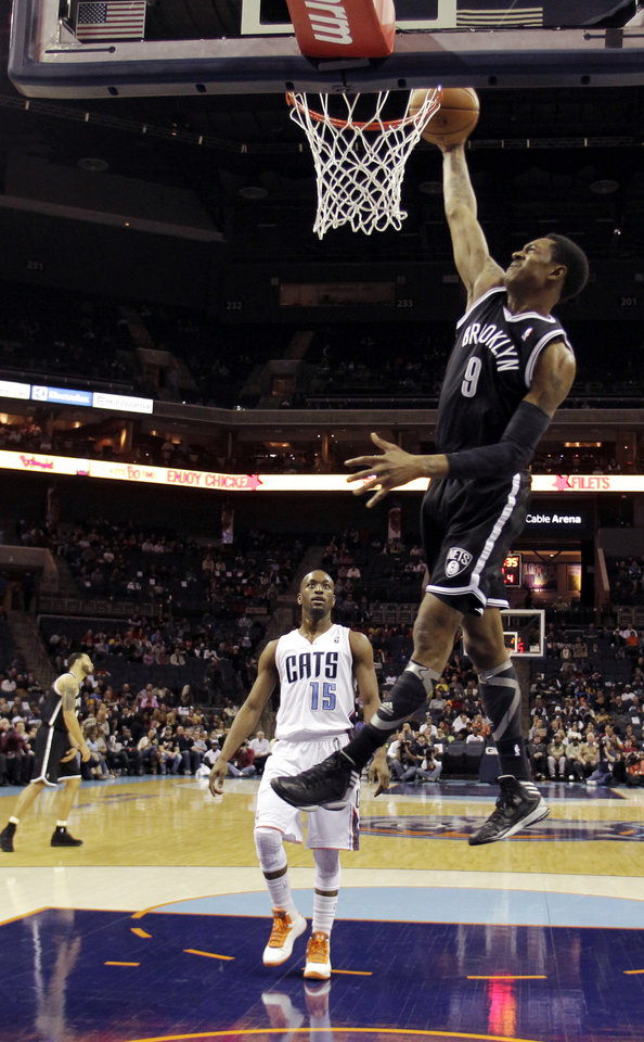 Photo - Brooklyn Nets' MarShon Brooks (9) dunks past Charlotte Bobcats' Kemba Walker (15) during the first half of an NBA basketball game in Charlotte, N.C., Wednesday, March 6, 2013. (AP Photo/Bob Leverone)