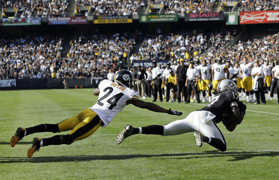 Photo -   Oakland Raiders wide receiver Denarius Moore, right, scores a touchdown on a six-yard pass as Pittsburgh Steelers cornerback Ike Taylor, left, looks on during the fourth quarter of an NFL football game in Oakland, Calif., Sunday, Sept. 23, 2012. Oakland won 34-31. (AP Photo/Marcio Jose Sanchez)