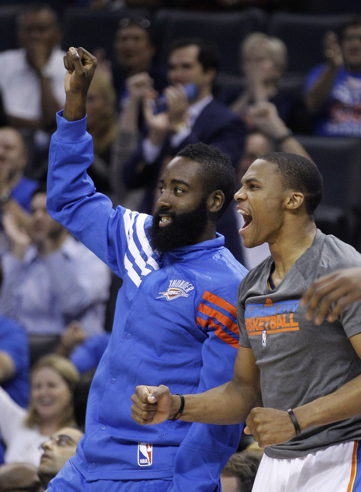 Photo -   Oklahoma City Thunder guard James Harden, left, and guard Russell Westbrook, right, react to a teammate's basket in the second quarter of a preseason NBA basketball game against the Charlotte Bobcats in Oklahoma City, Tuesday, Oct. 16, 2012. (AP Photo/Sue Ogrocki)