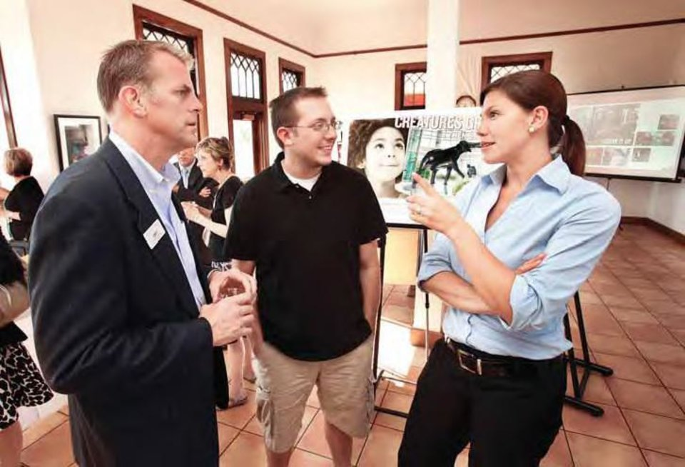 Stephen Koranda, executive director of the Norman Convention and Visitors Bureau, left, visits with resident Matt Lamey and Jen Tregarthen, also with the bureau, at the unveiling of the bureau's new logo at the Santa Fe Depot. OKLAHOMAN ARCHIVE PHOTO
