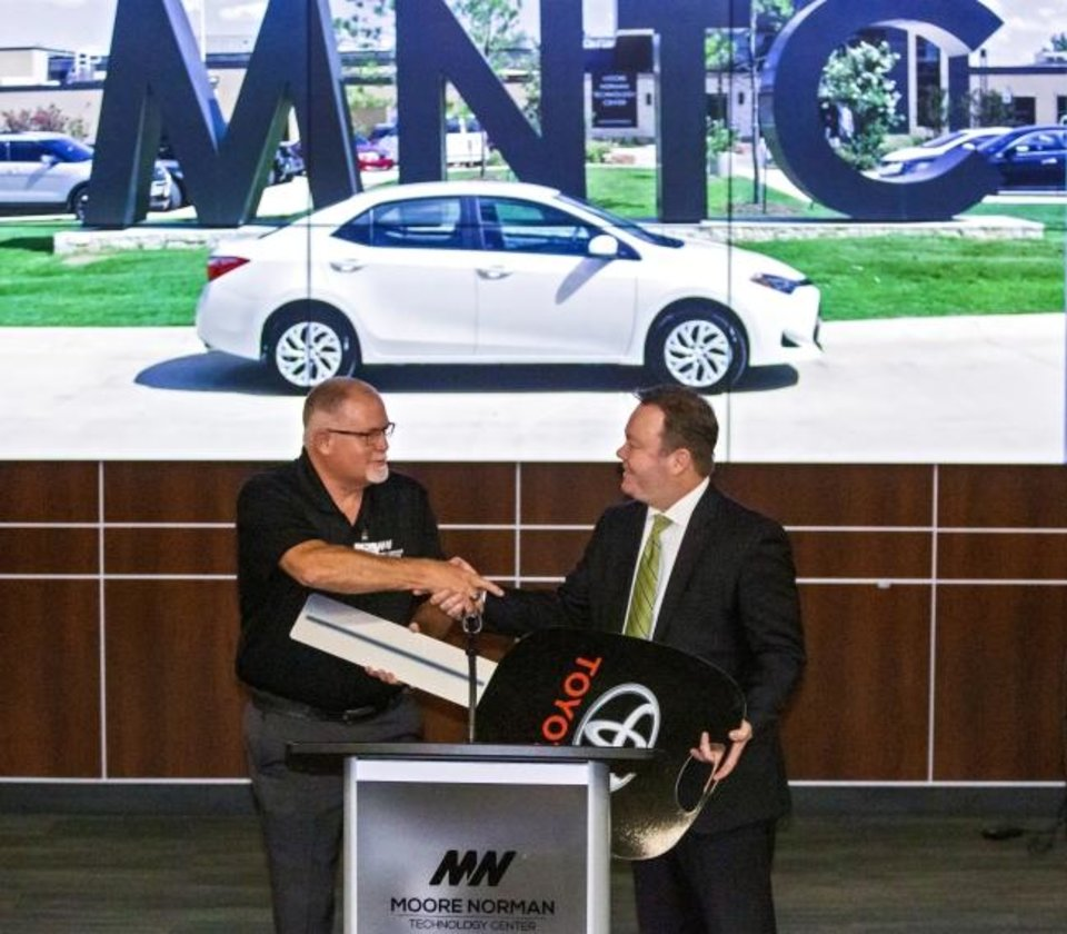 Photo -  Dallas McClary, Fowler Toyota General Manager, right, on Friday hands off the keys to Auto Service Technology Instructor, Lee Dow, to the new Toyota Corolla donated by Gulf States Toyota and Fowler Toyota to the Auto Technology program at Moore Norman Technology Center in Norman. [CHRIS LANDSBERGER/THE OKLAHOMAN]