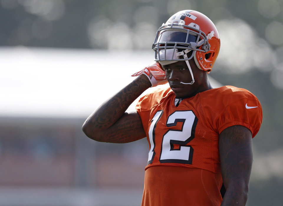 Photo - FILE - In this Aug. 4, 2014, file photo, Cleveland Browns wide receiver Josh Gordon rests during practice at the NFL football team's training campin Berea, Ohio. Gordon says the only place he can find peace is on the football field. His time there could be running short. The Browns' star receiver is awaiting word from the NFL on whether he'll be suspended for all or part of the season for violating the league's substance-abuse program. (AP Photo/Tony Dejak, File)
