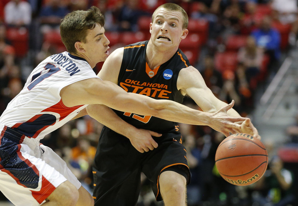 Photo - Oklahoma State's Phil Forte (13) passes around Gonzaga's David Stockton (11) during a second round game of the NCAA men's college basketball tournament at Viejas Arena in San Diego, between Oklahoma State and Gonzaga Friday, March 21, 2014. Photo by Bryan Terry, The Oklahoman