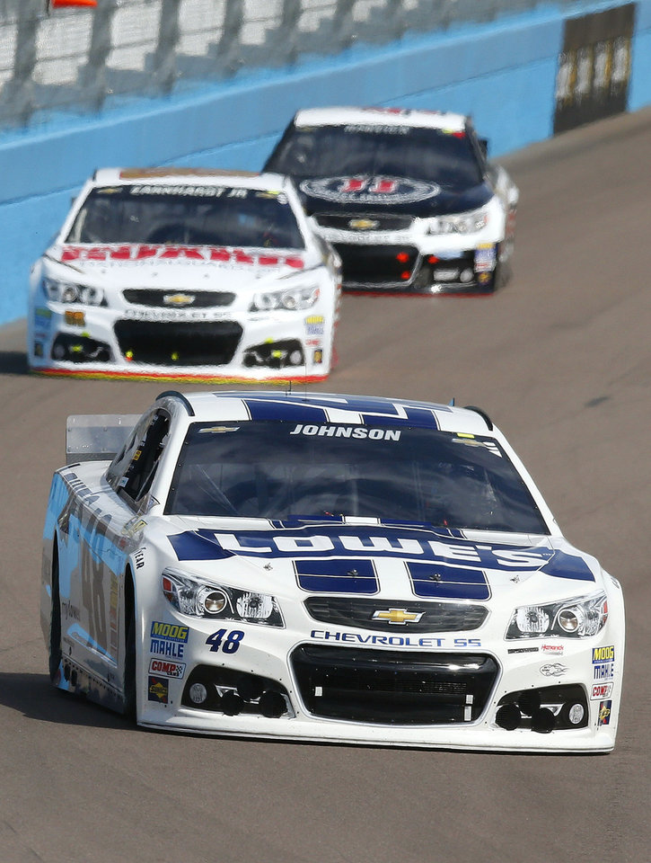 Photo - Jimmie Johnson (48), Dale Earnhardt, Jr., back left, and Kevin Harvick head into Turn 1 during the NASCAR Sprint Cup Series auto race Sunday, March 2, 2014, in Avondale, Ariz. (AP Photo/Ross D. Franklin)