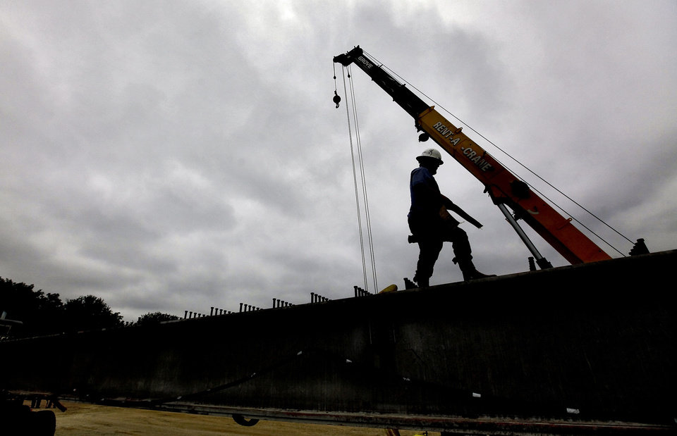 Photo - Crews work Monday to unload two 20,000-pound steel beams in Edmond that were the first to be removed from the old Interstate 40 Crosstown bridge. The two 90-foot beams will be part of the Deer Creek flood control bridge project on MacArthur near Covell. There will be a total of 1,914 beams removed from I-40 to be repurposed in bridge projects across the state.  Photo by Chris Landsberger, The Oklahoman
