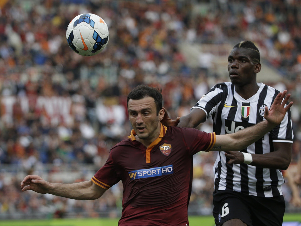 Photo - Roma defender Vasilis Torosidis, of Greece, left, and Juventus midfielder Paul Pogba, of France, vie for the ball during an Italian Serie A soccer match between Roma and Juventus at Rome's Olympic stadium, Sunday, May 11, 2014. (AP Photo/Alessandra Tarantino)