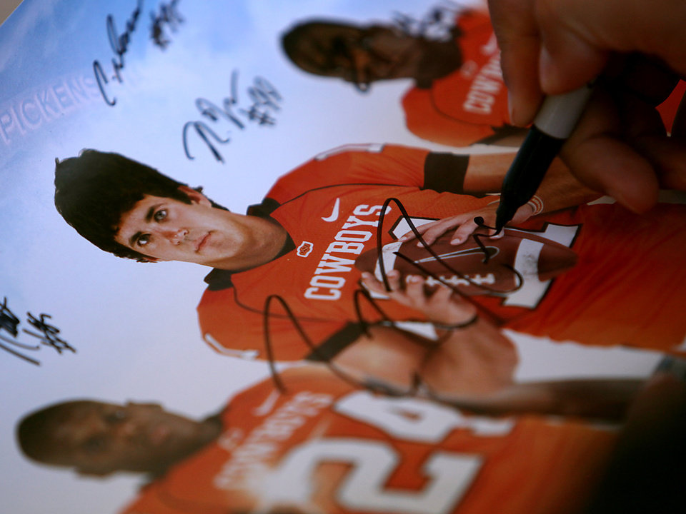 Oklahoma State quarterback Zac Robinson signs a poster for a fan during OSU\'s Fan Appreciation Day on Saturday in Stillwater. (Photo by John Clanton, The Oklahoman)