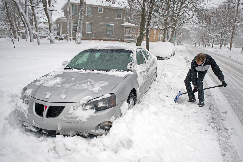 Photo - Jonathan Hines digs his car out of the snow on State Street, in Lafayette, Ind., on Monday, March 25, 2013, after a record-setting storm dumped more than 7 inches of snow in the area, bringing plows out in force and keeping police busy chasing a string of slide-offs. (AP Photo/The Journal & Courier, Brent Drinkut) MANDATORY CREDIT; NO SALES   .