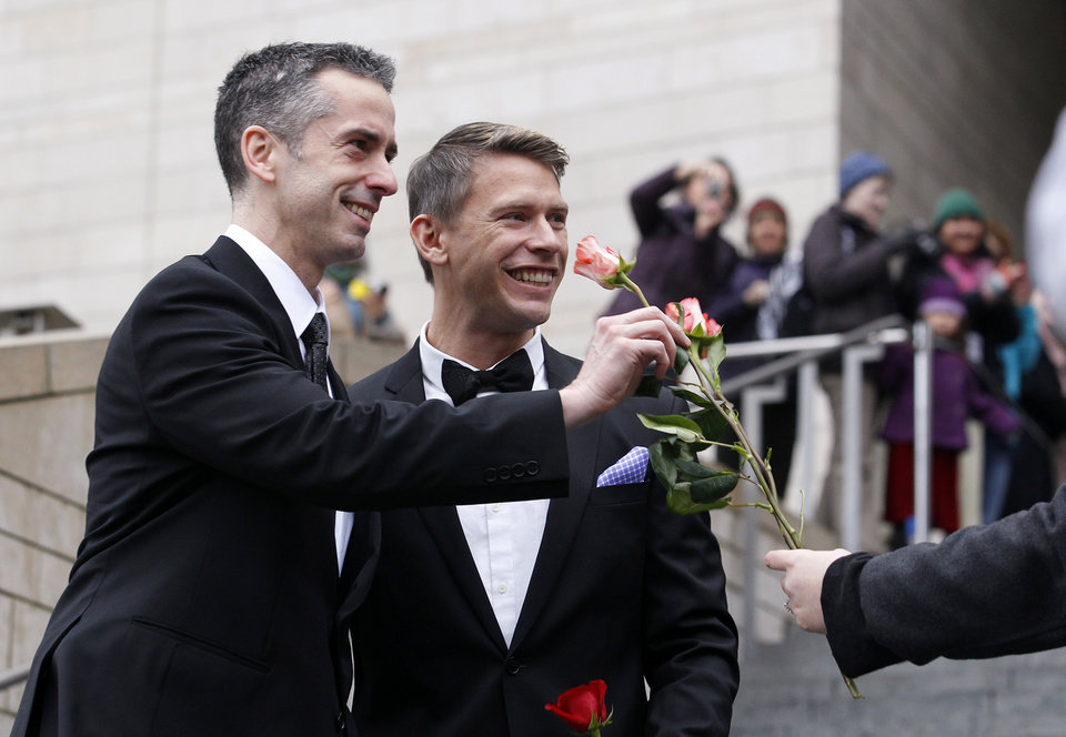 Photo - Dan Savage, left, and his husband Terry Miller are handed flowers after their wedding at Seattle City Hall, Sunday, Dec. 9, 2012, in Seattle. Gov. Chris Gregoire signed a voter-approved law legalizing gay marriage Wednesday, Dec. 5 and weddings for gay and lesbian couples began in Washington state on Sunday, following the three-day waiting period after marriage licenses were issued earlier in the week. (AP Photo/Elaine Thompson)