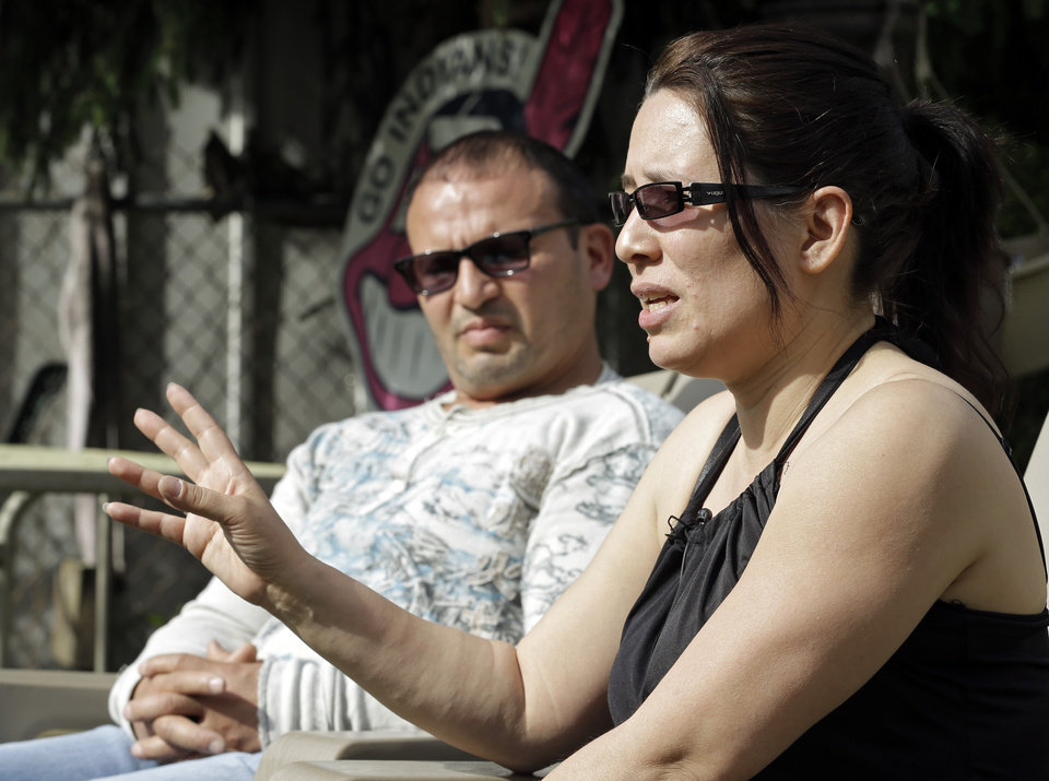 Photo - Elida Caraballo, right, talks about the abuse her late sister, Grimilda Figueroa, suffered at the hands of her common law husband, Ariel Castro, during an interview with her husband, Frank, at their home in Cleveland Thursday, May 9, 2013. Castro has been charged with kidnapping and rape for holding three women captive for a decade in his Cleveland home. (AP Photo/Mark Duncan)