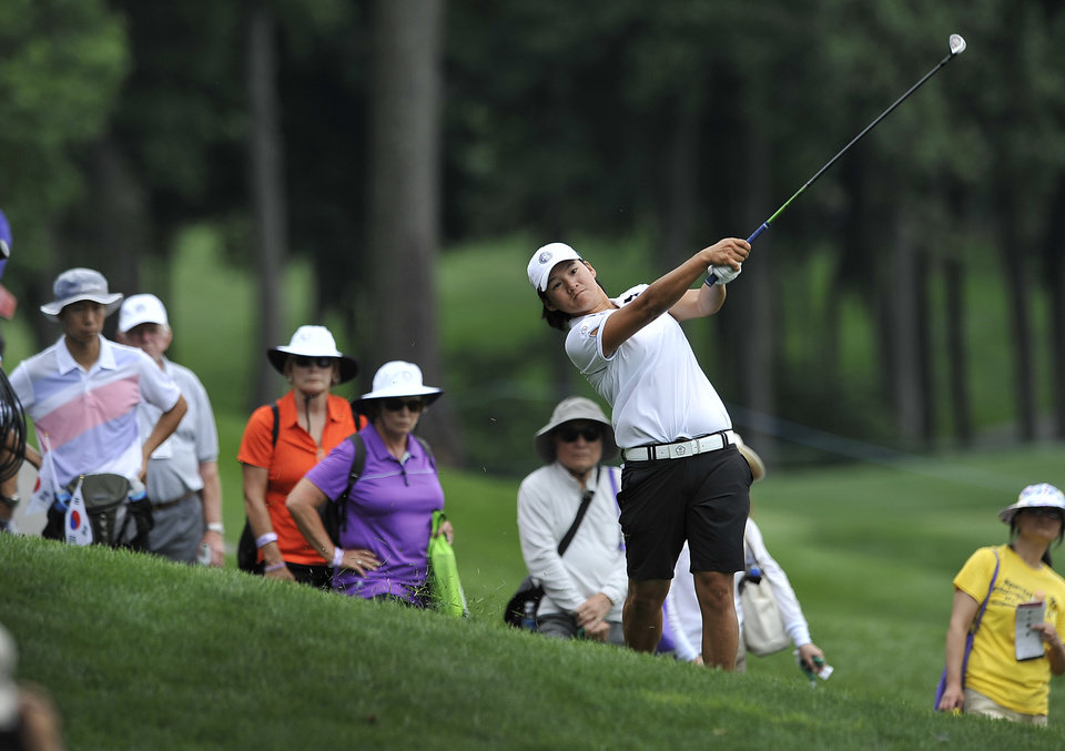 Photo - Yani Tseng, of Taiwan, follows through from the rough on the seventh hole during the first round of the International Crown golf tournament Thursday, July 24, 2014, in Owings Mills, Md.(AP Photo/Gail Burton)