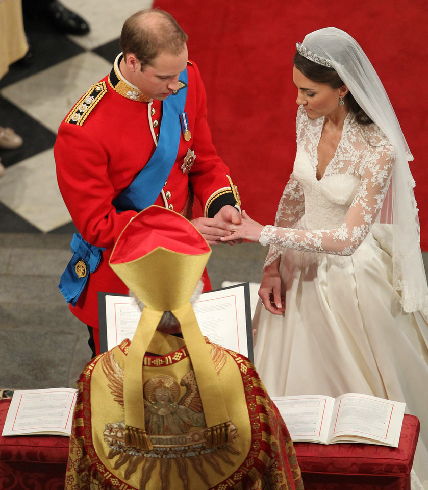 Photo - Prince William places the ring on the hand of Kate Middleton, at Westminster Abbey during their wedding service at Westminster Abbey, central London, Friday April 29, 2011. (AP Photo/Andrew Milligan, Pool)  ORG XMIT: RWAJP118