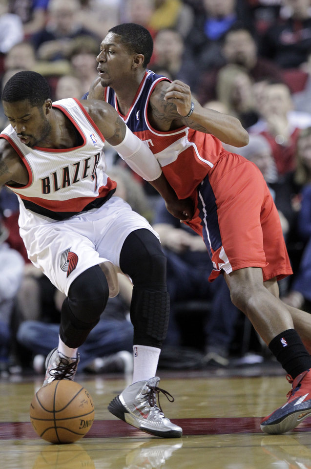 Photo - Washington Wizards guard Bradley Beal, right, plays tight defense on Portland Trail Blazers guard Wesley Matthews during the first half of an NBA basketball game in Portland, Ore., Thursday, March 20, 2014. (AP Photo/Don Ryan)