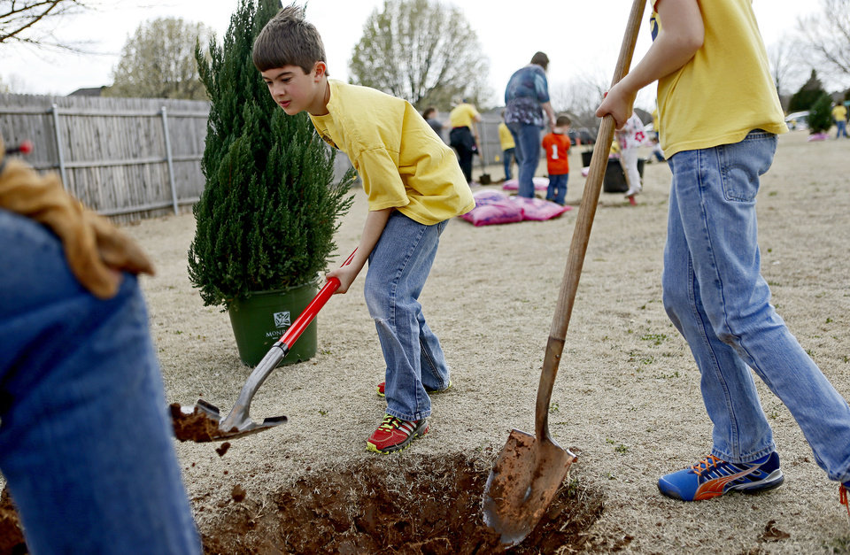 Photo - Above: Tanner Taylor, 10, with Cub Scout Pack 91, digs a hole for one of the 26 trees planted at Edmond's Westborough Park for Arbor Week. PHOTOS BY BRYAN TERRY, THE OKLAHOMAN
