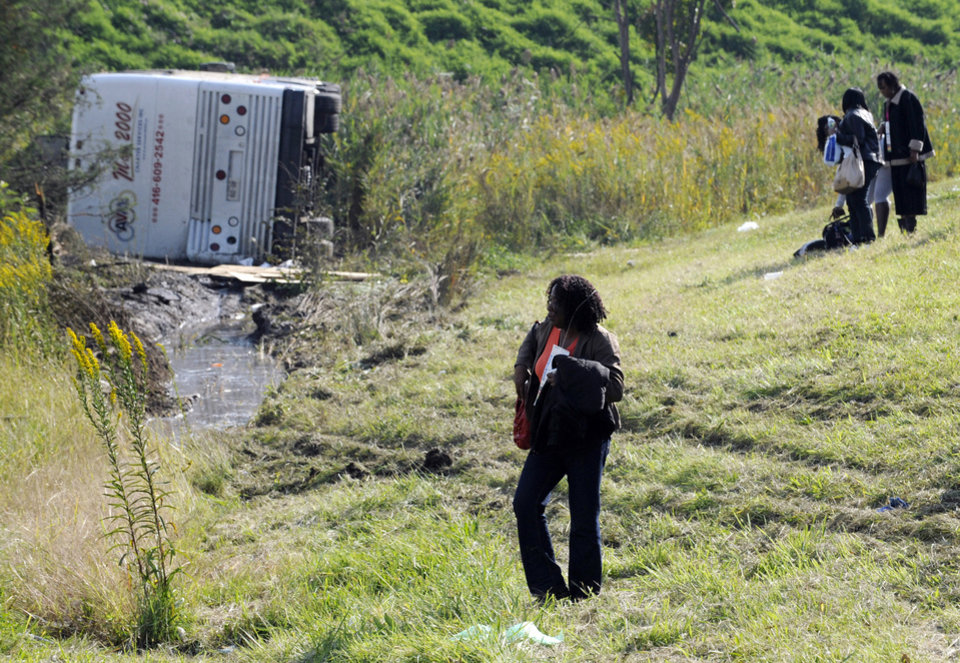 Photo -   Passengers look on after their bus overturned in a ditch at an exit ramp off Route 80 in Wayne, N.J. Saturday, Oct. 6, 2012. The chartered tour bus from Toronto carrying about 60 people overturned on an interstate exit ramp. Three people have been taken to hospital with non-life-threatening injuries. (AP Photo/Bill Kostroun)
