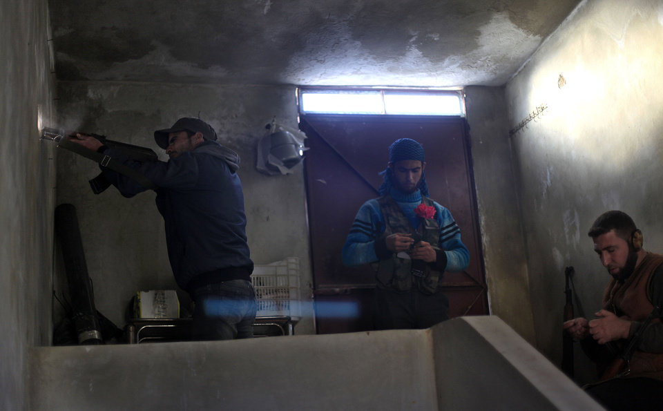 Photo - FILE - In this Saturday, Nov. 17, 2012 file photo, a Syrian fighter fires his weapon during clashes with Syrian army forces in town of Harem on the outskirts of Idlib, Syria. Through mid-2012, rebel power grew and Assad's army ramped up its response. Relentless government shelling leveled neighborhoods and killed hundreds. Regular reports emerged of mass killings by the regime or thugs loyal to it, pushing more Syrians toward armed struggle. The government, which considers the opposition terrorist gangs backed by foreign powers, denied any role, and does not respond to requests for comment on its military. The rebels, too, were accused of atrocities. (AP Photo/ Khalil Hamra, File)