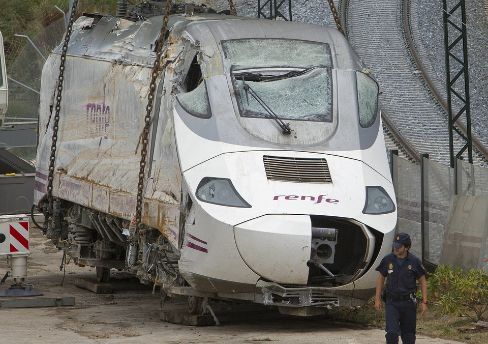 Photo - Police stand guard as a wreckage of a crashed train is seen ready to be deposited in Santiago de Compostela, Spain, Sunday July 28, 2013. Spain's interior minister Jorge Fernandez Diaz says the driver whose speeding train crashed, killing 78 people, is now being held on suspicion of negligent homicide. The Spanish train derailed at high speed Wednesday killing 78 and injuring dozens more. (AP Photo/Lalo R. Villar)
