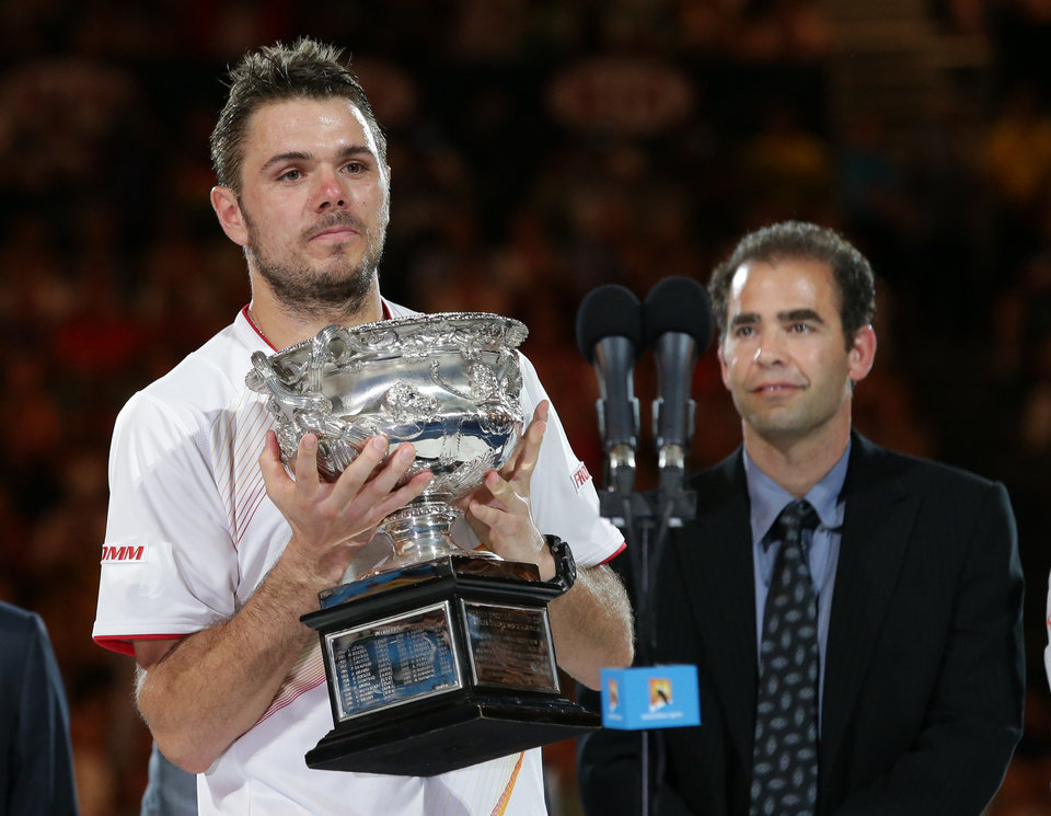 Photo - Stanislas Wawrinka of Switzerland holds the trophy after defeating Rafael Nadal of Spain, beside Pete Sampras,  in the men's singles final at the Australian Open tennis championship in Melbourne, Australia, Sunday, Jan. 26, 2014.(AP Photo/Aaron Favila)