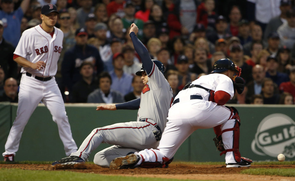 Photo - Atlanta Braves' Freddie Freeman, center, slides home safely as Boston Red Sox catcher David Ross gets the throw while starting pitcher Jake Peavy, left, looks on during the fourth inning of a baseball game at Fenway Park, Thursday, May 29, 2014, in Boston. (AP Photo/Winslow Townson)