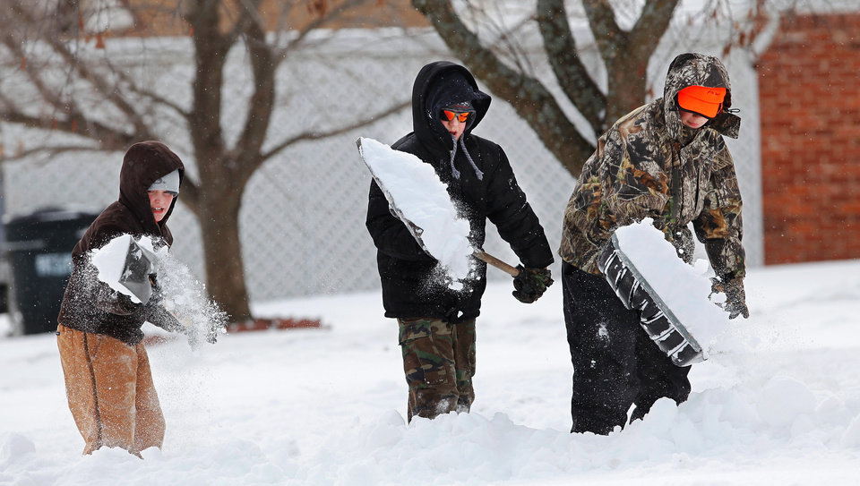 Photo - From left, buddies James Allison, 11, Jacob Freitas, 13, and Tristian Bargewell, 12, grabbed shovels and set out Wednesday morning asking neighbors in their Del City neighborhood  to hire the trio to clear snow from their sidewalks and driveways. The boys are pictured clearing a driveway on a street called Wofford.  The boys said they teamed last summer to operate a lemonade stand to earn extra spending cash.  A second winter storm in a week dumped about 6 inches of snow in the Oklahoma City area Tuesday morning, Feb. 9, 2011.   Photo by Jim Beckel, The Oklahoman