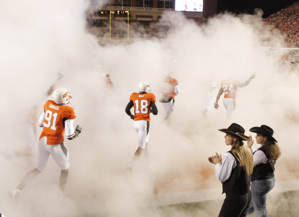 Photo - The Cowboys run onto the field during the college football game between Oklahoma State University (OSU) and the University of Missouri (MU) at Boone Pickens Stadium in Stillwater, Okla. Saturday, Oct. 17, 2009.  Photo by Doug Hoke, The Oklahoman