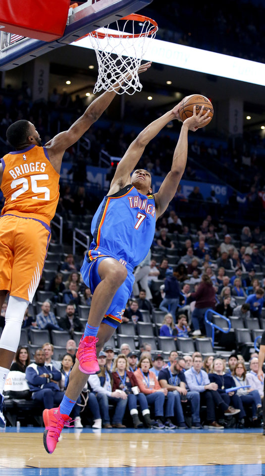 Photo - Oklahoma City's Darius Bazley (7) goes up for a basket as Phoenix's Mikal Bridges (25) defends during the NBA basketball game between the Oklahoma City Thunder and the Phoenix Suns at the Chesapeake Energy Arena in Oklahoma City , Friday, Dec. 20, 2019.   [Sarah Phipps/The Oklahoman]