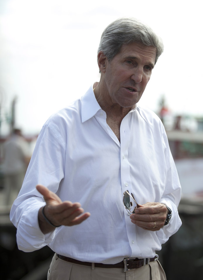 Photo - U.S. State Secretary John Kerry speaks to the media during a visit to a tuna packaging factory in Bali, Indonesia, Sunday, Oct. 6, 2013. Kerry said Sunday that a pair of U.S. military raids against militants in North Africa sends the message that terrorists