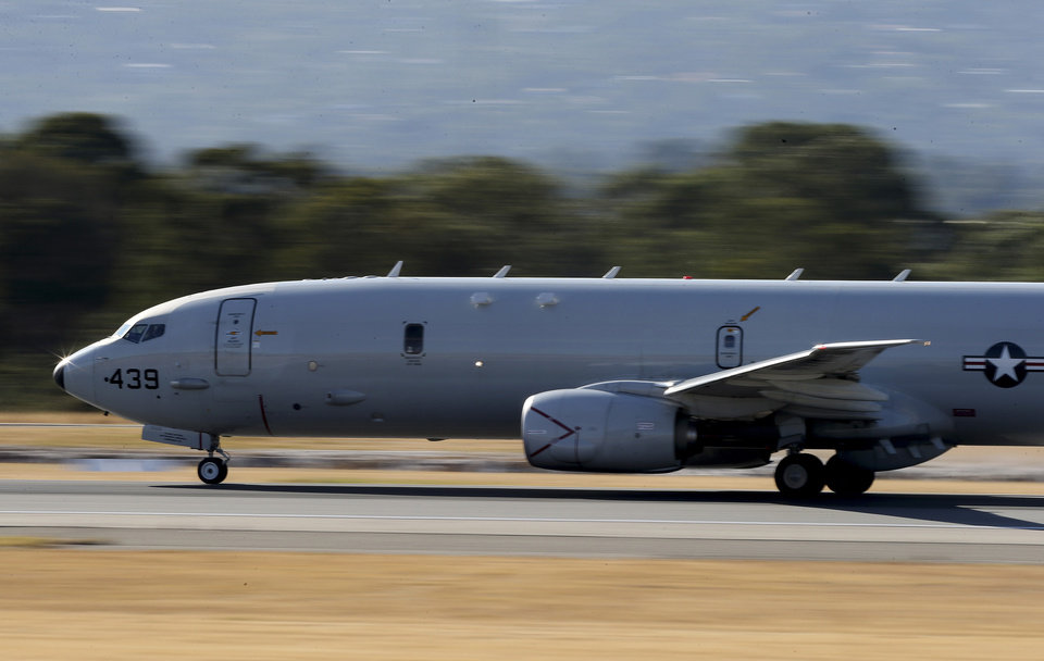 Photo - A U.S. Navy P-8 Poseidon takes off from Perth Airport on route to rejoin the on-going search operations for the missing Malaysia Airlines Flight 370 in Perth, Australia, Thursday, April 10, 2014. Planes and ships hunting for the missing Malaysian jetliner zeroed in on a targeted patch of the Indian Ocean on Thursday, after a navy ship picked up underwater signals that are consistent with a plane's black box. (AP Photo/Rob Griffith)