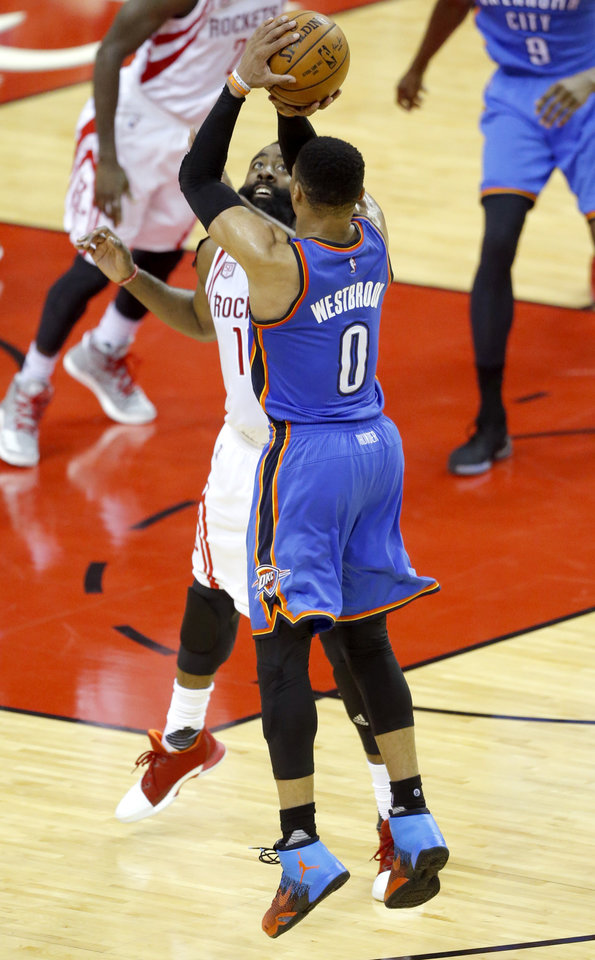 Photo - Oklahoma City's Russell Westbrook (0) shoot a 3-point basket over Houston's James Harden (13) during Game 5 in the first round of the NBA playoffs between the Oklahoma City Thunder and the Houston Rockets in Houston, Texas,  Tuesday, April 25, 2017.  Houston won 105-99. Photo by Sarah Phipps, The Oklahoman
