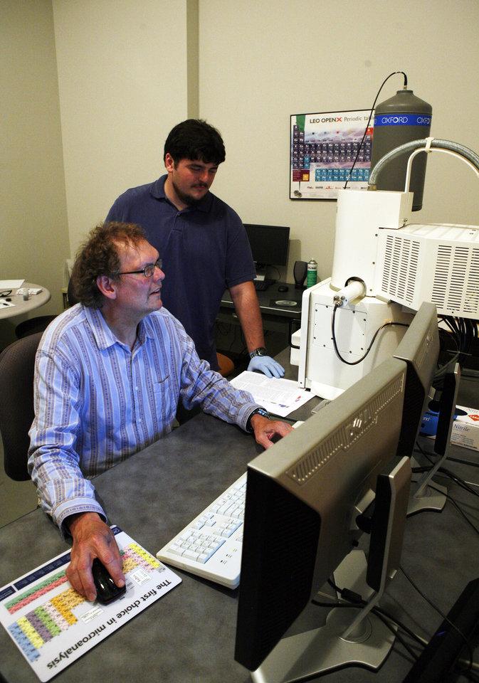 Photo - In this photo taken Monday, June 2, 2014, Kurt Sickfus, a professor at the University of Tennessee (seated), works with PhD student Devin Roberts on the Scanning Electron Microscope in Knoxville, Tenn., and is among several researchers involved in efforts to make accident-resistant fuel for the nuclear industry. (AP Photo/Wade Payne)