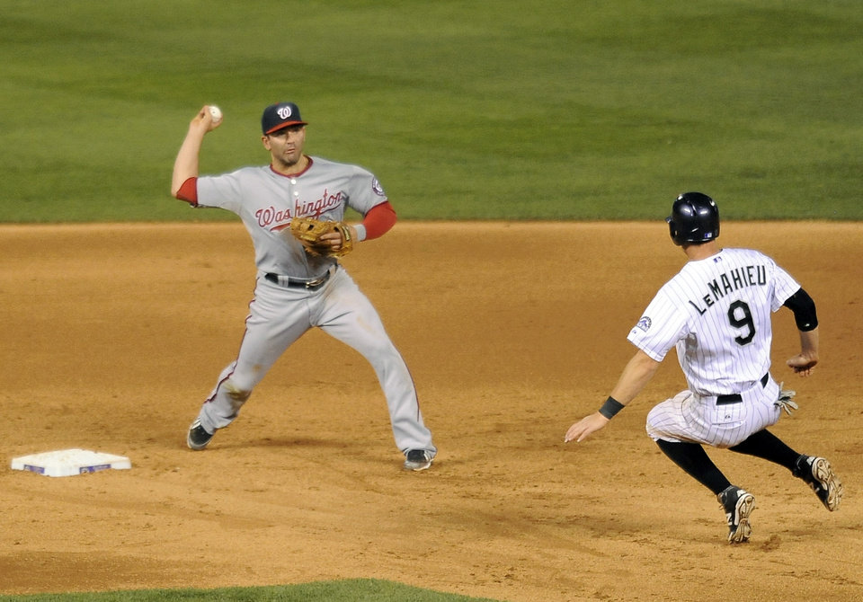 Photo - Colorado Rockies DJ LeMahieu, right, is forced out at second base by Washington Nationals second baseman Danny Espinosa in the sixth inning of a baseball game on Tuesday, July 22, 2014, in Denver. (AP Photo/Chris Schneider)