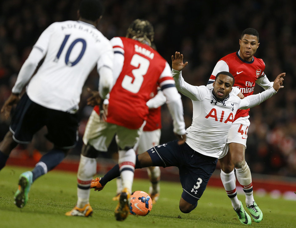 Photo - Tottenham's Danny Rose, second right falls from the challenge of Arsenals' Serge Gnaby, right, during the English FA Cup third round soccer match between Arsenal and Tottenham Hotspur at the Emirates Stadium in London, Saturday, Jan. 4, 2014. (AP Photo/Kirsty Wigglesworth)