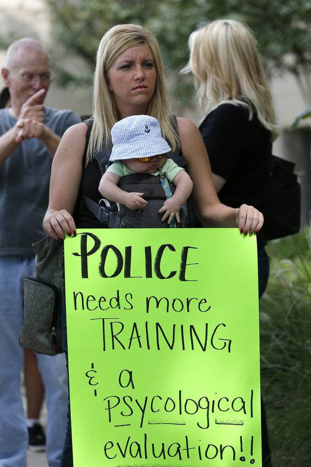 Photo - Maegan Grigg holds a sign with her baby Cayden Tood, 5 months, during the Justice for Magdiel Sanchez rally in Oklahoma City, Sunday, Sept. 24, 2017. Photo by Sarah Phipps, The Oklahoman