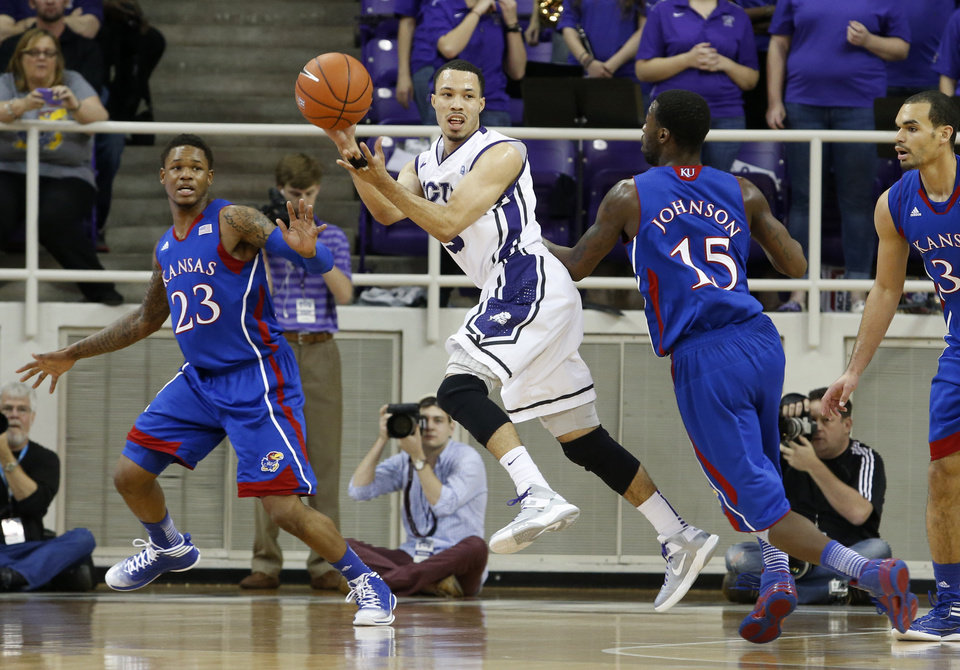 Photo - TCU guard Kyan Anderson (5) passes the ball under pressure from Kansas guards Ben McLemore (23) and Elijah Johnson (15) during the first half of an NCAA college basketball game Wednesday, Feb. 6, 2013, in Fort Worth, Texas. (AP Photo/Sharon Ellman)