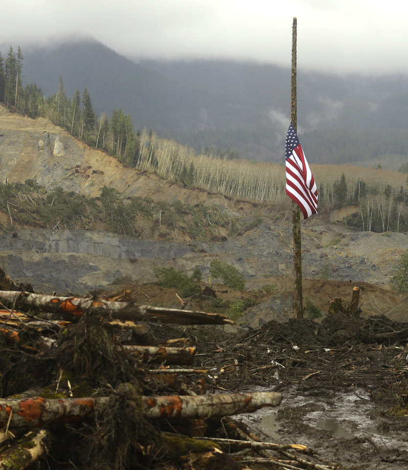 Photo - ALTERNATE CROP - A flag flies at half-staff on a log Sunday, March 30, 2014, with the slope of the massive mudslide that struck Saturday, March 22, 2014 in the background. The search for victims of the deadly slide continued Sunday, with crews searching both with heavy machinery and by hand. (AP Photo/Ted S. Warren)