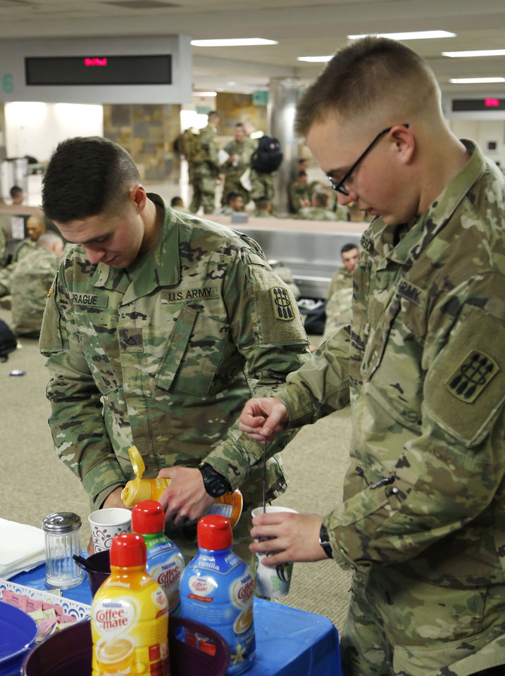 Photo - Tyler Sprague, from New Jersey, left, and Allan Larson, from Washington, prepare their coffee, as soldiers from Ft. Sill gather at Will Rogers World Airport in Oklahoma City, Okla. on their way home for Christmas, Monday, Dec. 19, 2016.  Photo by Paul Hellstern, The Oklahoman