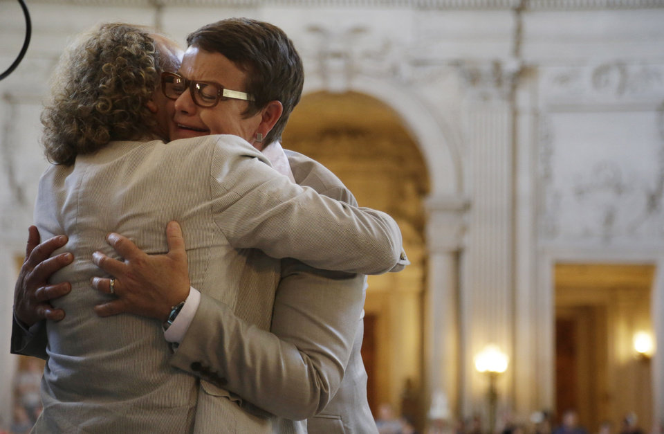 Photo - Kris Perry, right, is hugged by a supporter after marrying Sandy Stier in a ceremony presided by California Attorney General Kamala Harris at City Hall in San Francisco, Friday,  June 28, 2013. Stier and Perry, the lead plaintiffs in the U.S. Supreme Court case that overturned California's same-sex marriage ban, tied the knot about an hour after a federal appeals court freed same-sex couples to obtain marriage licenses for the first time in 4 1/2 years. (AP Photo/Marcio Jose Sanchez)