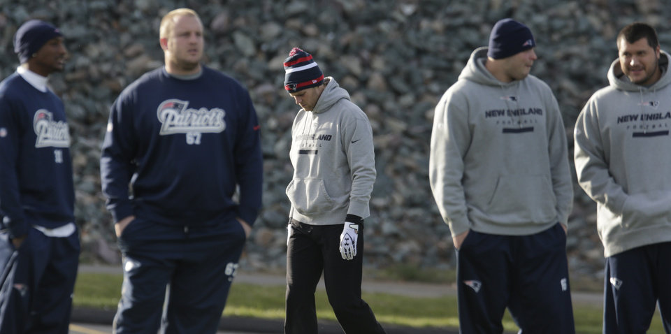 New England Patriots quarterback Tom Brady, center, walks past teammate as he heads to the field prior to NFL football practice in Foxborough, Mass., Tuesday, Nov. 20, 2012. (AP Photo/Charles Krupa)