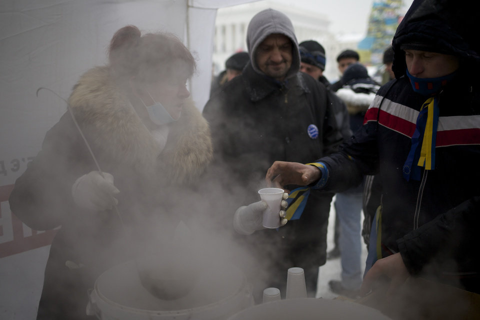 Photo - A volunteer distributes hot tea for Pro-European Union activists gathered on the Independence Square in Kiev, Ukraine, Monday, Dec. 9, 2013.  The protesters rose up against President Viktor Yanukovych after he spiked a deal for integration with the European Union and decided to restore trade ties with Russia instead. (AP Photo/Alexander Zemlianichenko)
